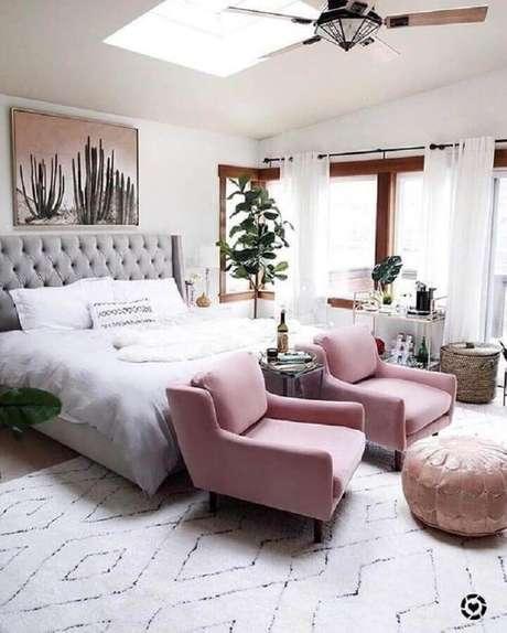 21. Poltrona para quarto de casal amplo decorado com vaso de planta e cabeceira capitonê – Foto: Article