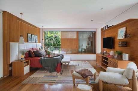 42. Poltrona para quarto de casal amplo com revestimento e móveis de madeira – Foto: Escala Arquitetura