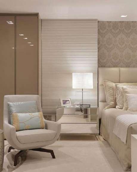 50. Poltrona pequena para quarto de casal decorado em tons neutros e criado mudo espelhado – Foto: Dicas Decor