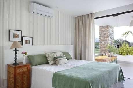16. É interessante associar a cor do papel de parede listrado à roupa de cama. Projeto de RBP Arquitetura e Interiores
