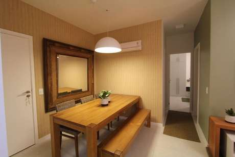 29. Este papel de parede listrado amarelo combina muito com os móveis de madeira. Projeto de Isabela Lavenere