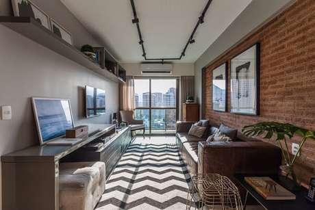 8. Apartamento pequeno com parede de tijolinhos e tapete chevron preto e branco. Fonte: Pinterest