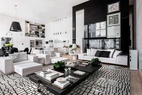 24. Sala de estar ampla com tapete preto e branco com design craquelado. Projeto por Lídia Maciel