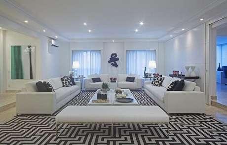 25. Sala de estar com decoração clássica conta com a presença de um tapete preto e branco. Projeto por Figueiredo Fischer