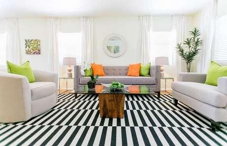 37. Sala de estar clean com almofadas coloridas e tapete preto e branco listrado. Fonte: Decoist
