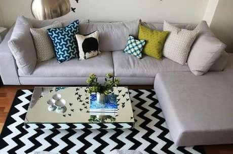 27. Sala de estar com sofá cinza e tapete preto e branco chevron. Fonte: Construção e Design