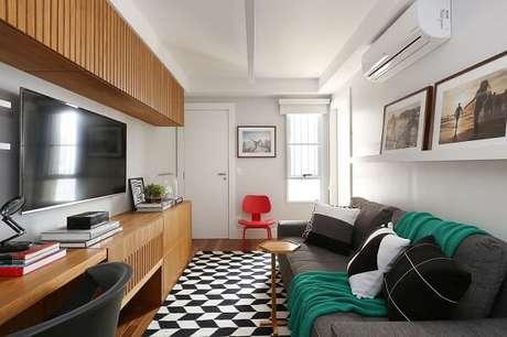 32. Sala de estar pequena com sofá cinza e tapete preto e branco. Projeto por ACF Arquitetura