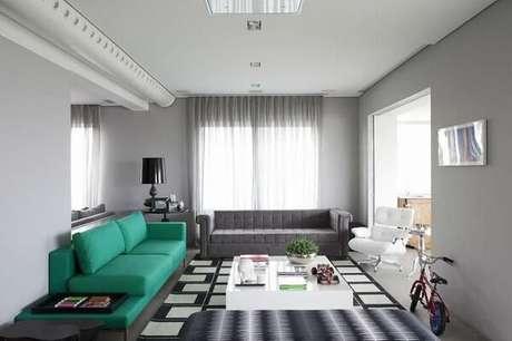 40. Sofá verde e tapete preto e branco encantam a decoração da sala de estar. Projeto por Triplex Arquitetura