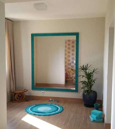 40. Moldura para espelho grande no tom azul turquesa combina com o tapete do ambiente. Fonte: Pinterest
