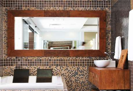 8. Moldura para espelho feito em madeira segue o mesmo material da bancada. Projeto por Colormix Para um Ambiente Ideal