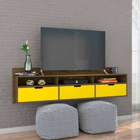 42. Este modelo de rack suspenso brinca com o amarelo e com o marrom da madeira. Foto: Mobly