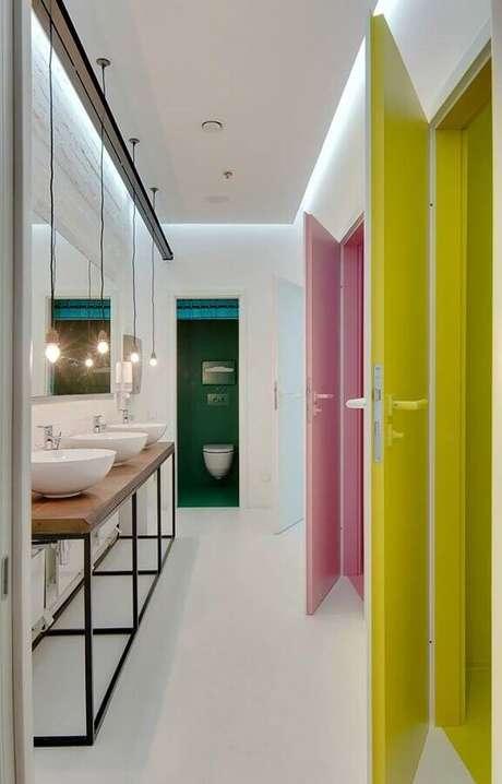 13. Decoração colorida para banheiro feminino coletivo com bancada de madeira e pendentes minimalistas – Foto: Archdaily