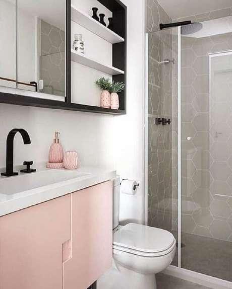 18. Decoração para banheiro feminino com gabinete rosa, nicho preto e revestimento cinza com formato hexagonal na área do box – Foto: Pinterest