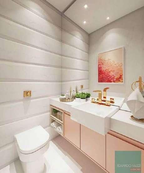 19. Banheiro feminino decorado com gabinete rosa e torneiras douradas dando um toque sofisticado -Foto: Eduardo Muzzi