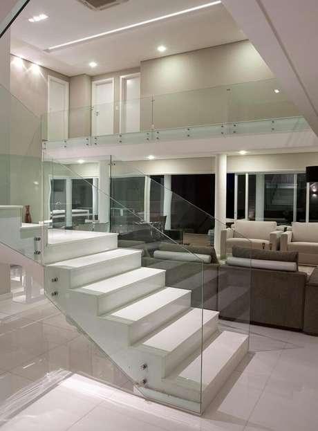 16. Sala com escada branca e guarda corpo de vidro temperado. Projeto por Gil Carlos de Camillo