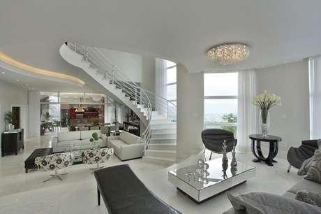 21. Sala com escada central encanta a decoração do cômodo. Projeto por Aquiles Nicolas Kílaris