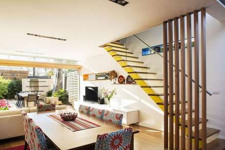 41. Sala com escada flutuante de madeira e guarda corpo de vidro. Fonte: Pinterest