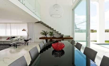44. Sala com escada flutuante, mesa preta e cadeiras cinza. Projeto por Espaço do Traço Arquitetura
