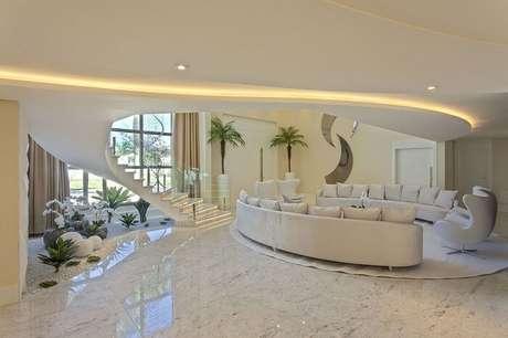 49. Sala de estar clean com escada caracol encanta a decoração. Projeto por Iara Kilaris