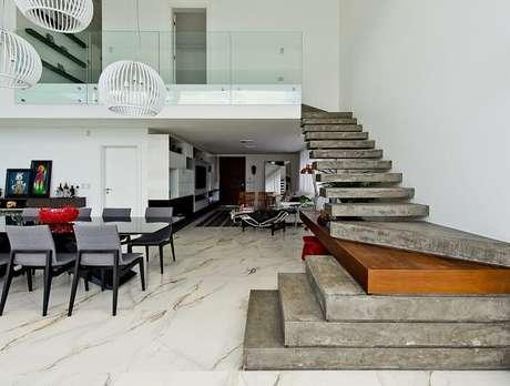 51. Sala de estar com escada de cimento. Projeto por Espaço do Traço Arquitetura