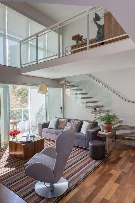 58. Sala de estar com escada flutuante e guarda corpo de vidro. Projeto por Ah! SIM