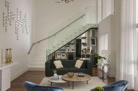 57. Sala com escada flutuante e guarda corpo de vidro temperado. Projeto por Érica Salguero