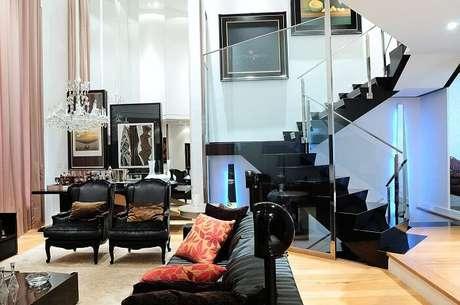 59. Sala de estar com escada preta encanta a decoração do espaço. Projeto por Moreno Interiores