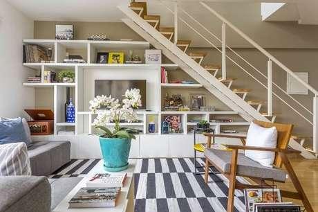 7. Sala pequena com escada de madeira e corrimão de ferro. Projeto por Hildebrand Silva Arquitetura