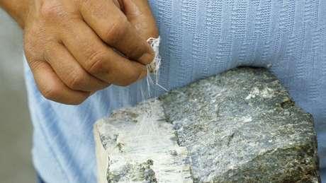 Um mineiro puxando fios de um pedaço de amianto branco