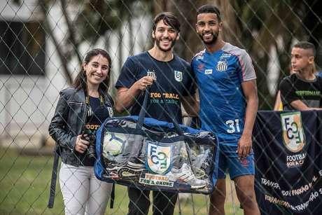 Manuella Carvalho e André Georges, da Football for a cause, e o lateral Jorge, do Santos: doação de materiais para projetos sociais