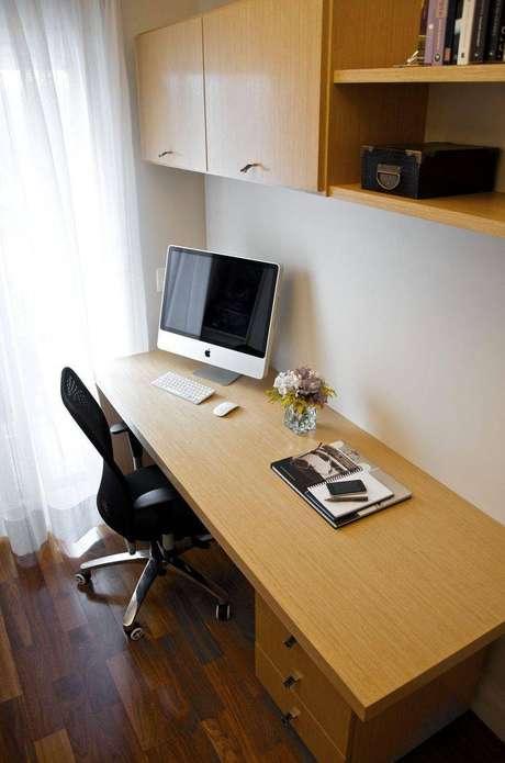 5. Essa escrivaninha para quarto clássica de madeira possui gavetas inclusas na mesa. Projeto de Danyela Correa