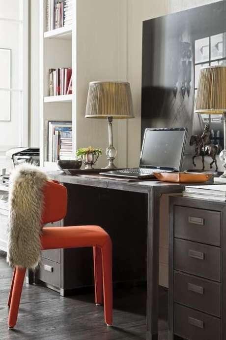 50. Escrivaninha para quarto de madeira escura com cadeira laranja. Projeto de Roberto Migotto