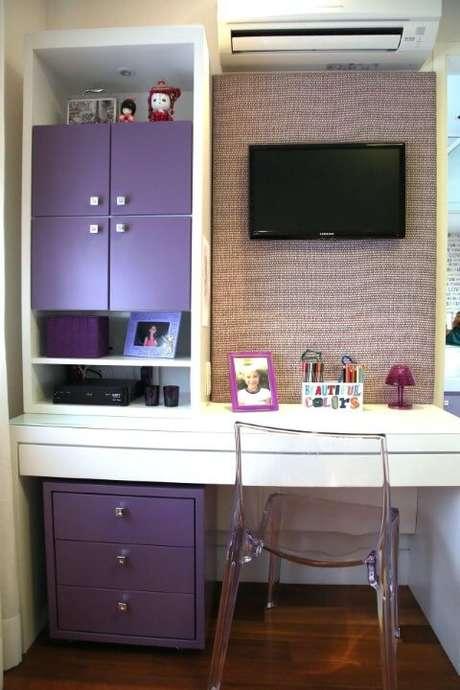 30. A decoração juvenil aqui é definida pelos itens de decoração e pela cor roxa, que contrasta bem com a escrivaninha do quarto. Projeto de Meyer Cortez