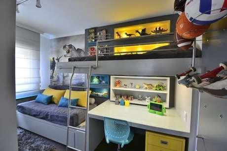 40. Escrivaninha para quarto integrada à cama suspensa ao cômodo com decoração de dinossauro. Projeto de BG Arquitetura