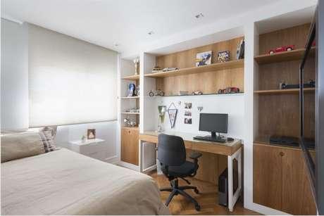 43. Escrivaninha para quarto de madeira com pés brancos combinando perfeitamente com o ambiente. Projeto de Gustavo Motta