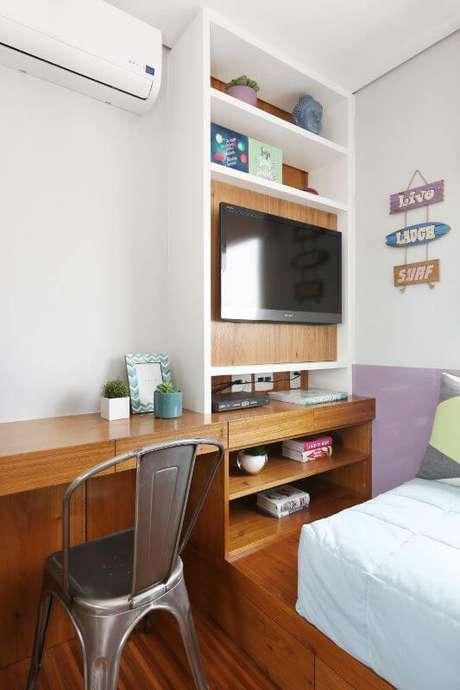 46. Escrivaninha para quarto de madeira embutida na decoração com cadeira industrial contrastando. Projeto de Bianchi Lima