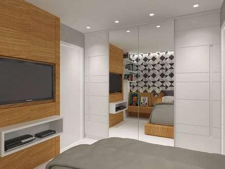 16. Decoração com painel de madeira e guarda roupa branco com espelho para quarto clean – Foto: Tripper Arquitetura