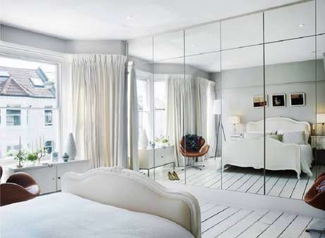 33. Decoração minimalista para quarto todo branco com guarda roupa grande com espelho – Foto: Desire to Inspire