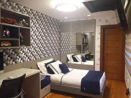 42. Guarda roupa solteiro com espelho para decoração de quarto masculino com papel de parede – Foto: Ideias Decor