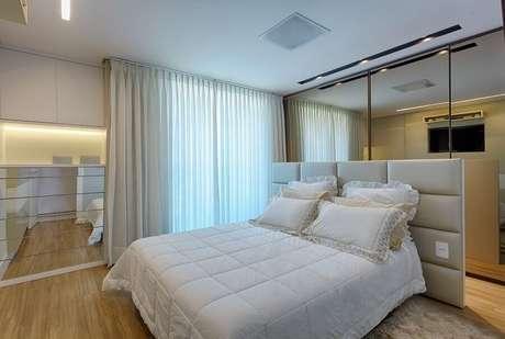 53. Suíte de casal decorada com cabeceira estofada e guarda roupa com espelho grande atrás da cama – Foto: Maria Laura Coelho