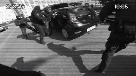 Amigo de Sergio é retirado do carro por atores vestidos como policiais