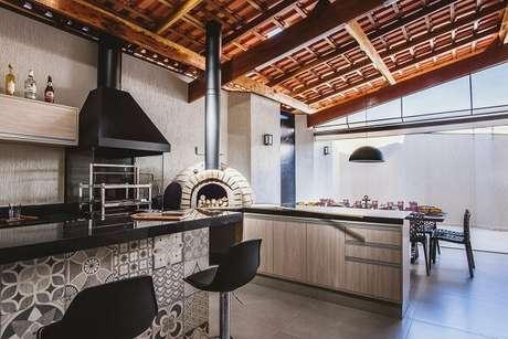 55- Área de churrasco com bancada de granito preto. Projeto por MAV Arquitetura