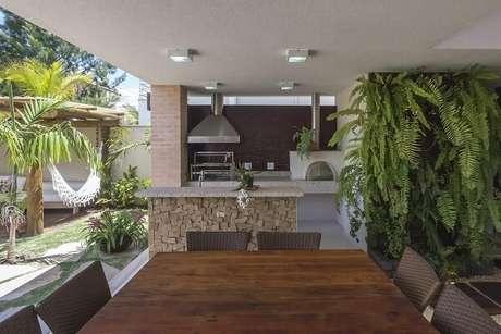 57- Área de churrasqueira com mesa de madeira. Projeto por Jannini Sagarra Arquitetura