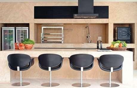 58- Área de churrasco com torneira gourmet e poltronas na cor preta. Projeto por A1 Arquitetura