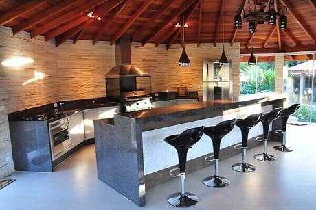 41. Área de churrasco moderna com bancada e banquetas altas.