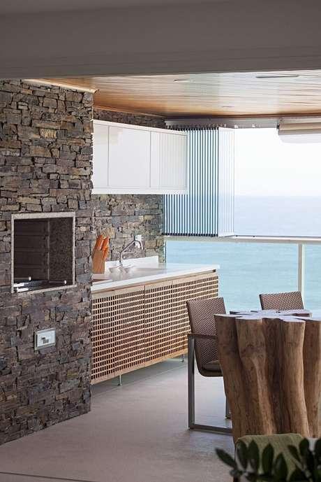65- Área de churrasqueira com bancada branca. Projeto por Korman Arquitetos
