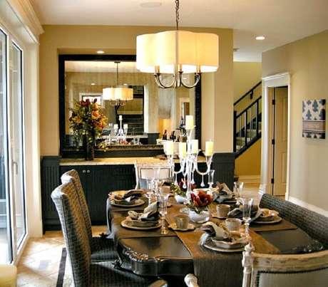 24. O espelho decorativo com moldura escura, casou com a decoração de sala de estar que tem móveis mais escuros.