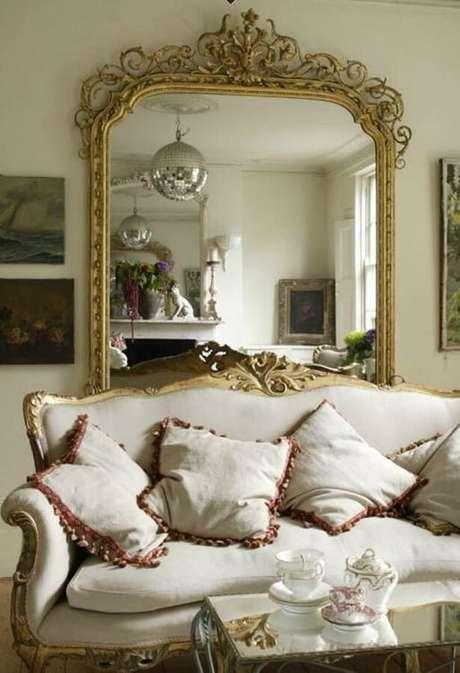 21. Decoração de sala com espelho em moldura clássica.