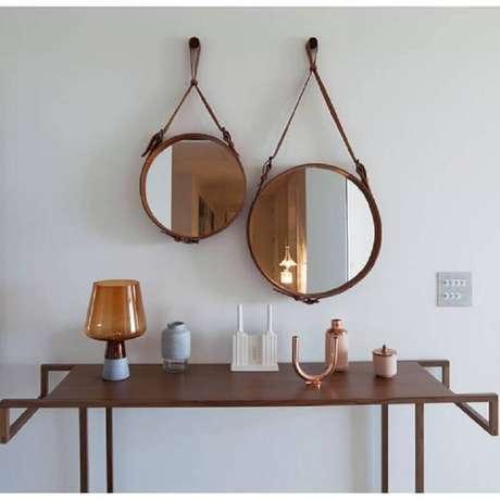 66. Os espelhos decorativos redondos com alça de couro são tendência na decoração – Foto: Archilovers