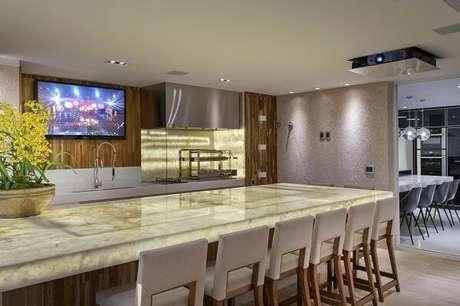 70- Varanda gourmet com churrasco de vidro e bancada de mármore iluminado. Projeto por Iara Kilaris